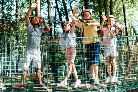 Photo pour Cheerful multicultural boys near friends in helmets waving hands in adventure park - image libre de droit