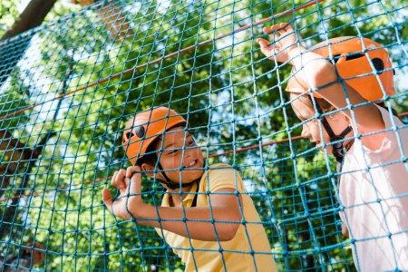 Photo pour Vue à angle bas de l'enfant heureux regardant garçon mignon à l'extérieur - image libre de droit