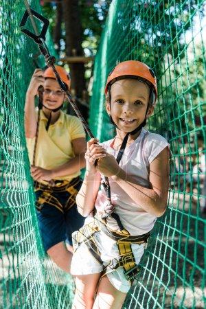 Foto de Enfoque selectivo de niños alegres en cascos con equipo de altura en el parque de aventuras - Imagen libre de derechos