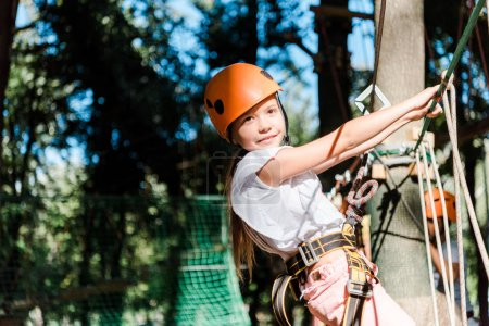 Photo pour Cheerful kid in helmet with height equipment in adventure park - image libre de droit