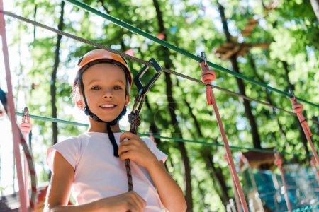 Foto de Vista de ángulo bajo de adorable niño en casco naranja sonriendo fuera - Imagen libre de derechos