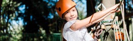 Foto de Plano panorámico de niño positivo con equipo de altura en el sendero de cuerda alta - Imagen libre de derechos