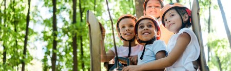Photo pour Panoramic shot of positive multicultural kids looking up in adventure park outside - image libre de droit
