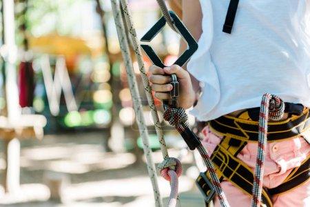 Photo pour Vue recadrée de l'enfant avec équipement de sécurité dans le parc d'aventure - image libre de droit