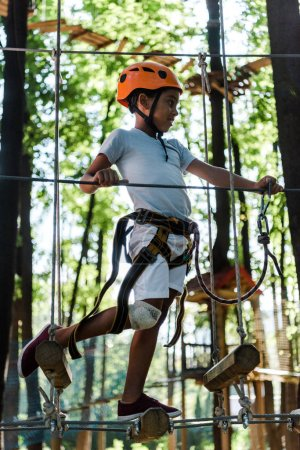Photo pour Happy african american child in orange helmet in adventure park - image libre de droit
