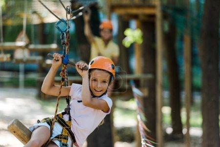 Foto de Enfoque selectivo de niño feliz y lindo en el casco en el parque de aventuras - Imagen libre de derechos