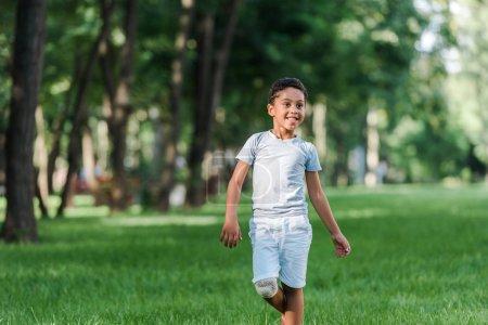 Photo pour Un garçon afro-américain gai sur de l'herbe verte dans le parc - image libre de droit