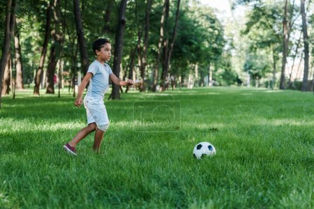 Photo for Adorable african american child playing football on green grass - Royalty Free Image