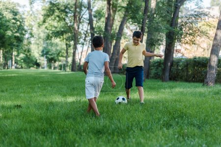 happy multicultural boys playing football on green grass