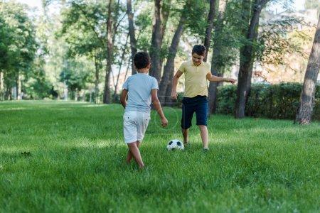 Foto de Happy multicultural boys playing football on green grass - Imagen libre de derechos