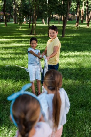 Photo for Selective focus of cheerful multicultural kids competing in tug of war outside - Royalty Free Image