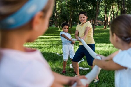 Photo for Selective focus of happy multicultural kids competing in tug of war outside - Royalty Free Image
