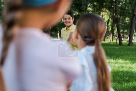 Photo for Selective focus of cheerful kids competing in tug of war outside - Royalty Free Image