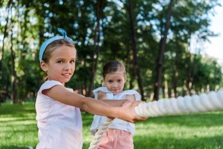 Photo for Happy and cute kids competing in tug of war outside - Royalty Free Image