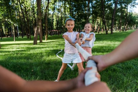 Photo for Selective focus of cheerful multicultural children competing in tug of war outside - Royalty Free Image