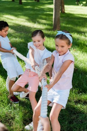 Photo for Selective focus of happy multicultural children competing in tug of war - Royalty Free Image