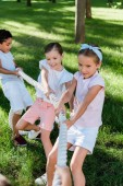 """Постер, картина, фотообои """"selective focus of happy multicultural children competing in tug of war """""""