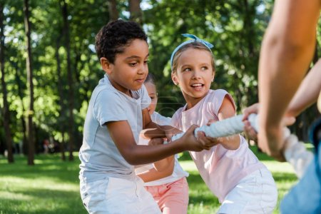 Photo for Cropped view of boy competing in tug of war with multicultural friends - Royalty Free Image