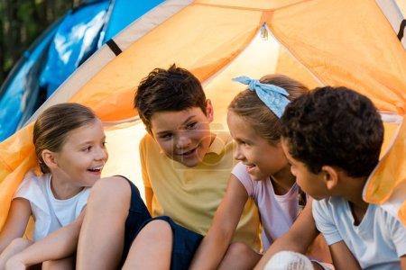 Foto de Niños multiculturales felices sentados en un campamento amarillo - Imagen libre de derechos
