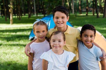 Foto de Happy multicultural kids smiling near camps in park - Imagen libre de derechos