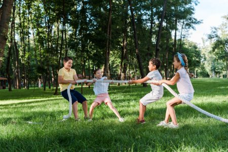 Photo for Cheerful multicultural kids competing in tug of war outside - Royalty Free Image