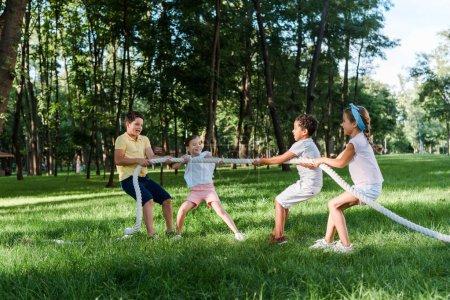 Foto de Niños multiculturales alegres compitiendo en tira y afloja fuera de la guerra - Imagen libre de derechos