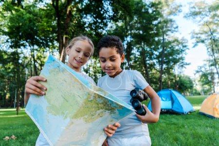 Photo pour Heureux enfants multiculturels regardant la carte près des camps - image libre de droit
