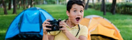panoramic shot of surprised boy holding digital camera near camps in park