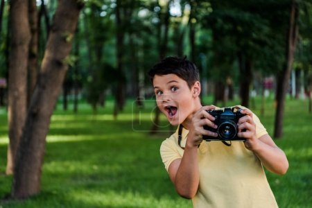 surprised boy holding digital camera in green park