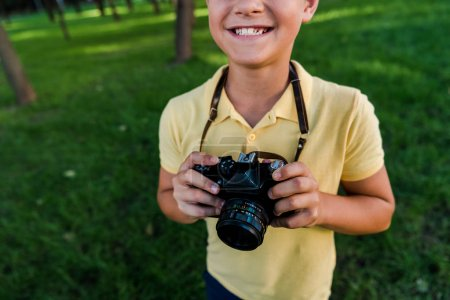 cropped view of happy boy holding digital camera in green park