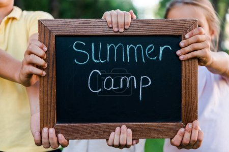 Photo for Cropped view of kids holding chalk board with summer camp letters - Royalty Free Image