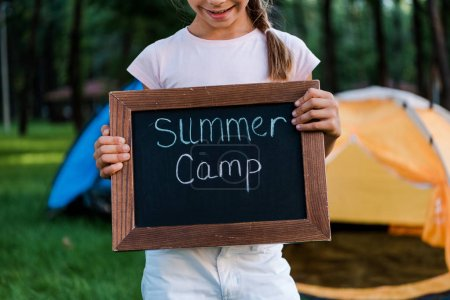 Photo for Cropped view of happy kid holding chalk board with summer camp letters - Royalty Free Image