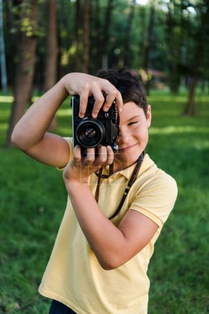 Photo for Positive boy taking photo while holding digital camera - Royalty Free Image