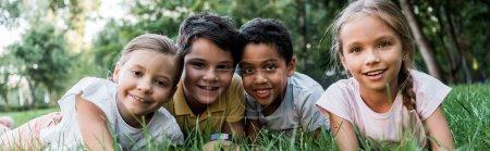 Photo pour Plan panoramique d'enfants multiculturels mignons allongés sur l'herbe - image libre de droit