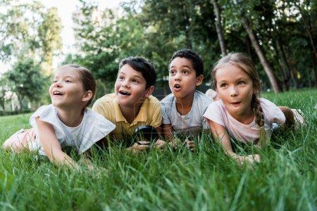 Photo pour Focalisation sélective d'enfants multiculturels surpris allongés sur l'herbe - image libre de droit