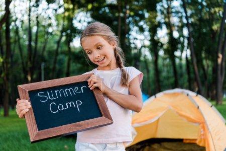 Glückliches Kind hält Kreidetafel mit Sommerlager-Briefen im Park