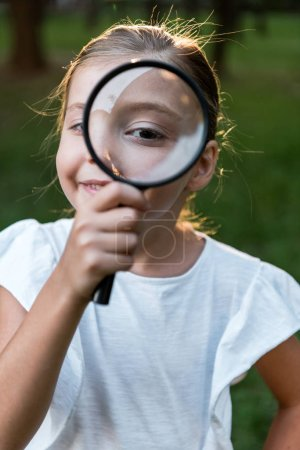 selective focus of cheerful kid holding magnifier near eye