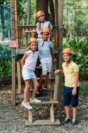 Photo pour Happy multicultural kids in helmets standing and smiling in adventure park - image libre de droit