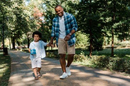 Photo pour Père américain africain heureux retenant des mains avec le fils tout en marchant sur le chemin dans le stationnement - image libre de droit