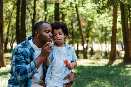 Photo pour Beau père américain africain et fils mignon soufflant la bulle de savon - image libre de droit