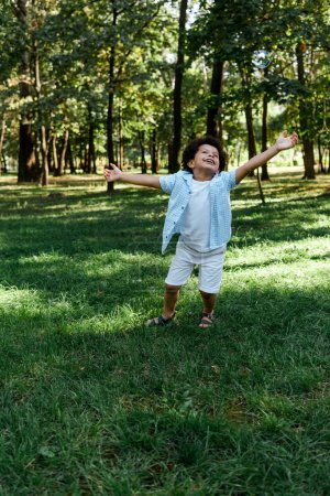 Photo for Happy african american kid with outstretched hands in park - Royalty Free Image