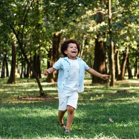 Foto de Niño afroamericano feliz corriendo sobre hierba verde en el parque - Imagen libre de derechos