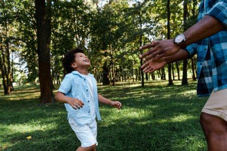 Photo pour Vue recadrée du père afro-américain avec les mains tendues près garçon heureux dans le parc - image libre de droit