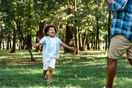 Photo for Happy african american kid running and looking at father - Royalty Free Image