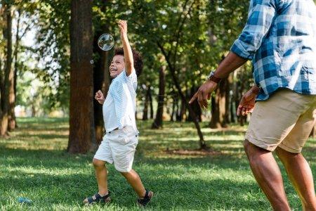 Foto de Vista recortada de padre señalando con el dedo cerca feliz hijo afroamericano gesturing en el parque - Imagen libre de derechos