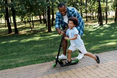 Photo pour Joyeux père afro-américain près heureux enfant sur scooter - image libre de droit
