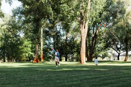 Photo for Happy african american son and father running on grass in park - Royalty Free Image