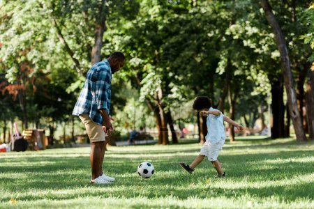 handsome african american man playing football with cute son