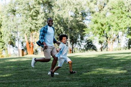 Photo pour Heureux père et fils d'Amérique africaine courant sur l'herbe - image libre de droit