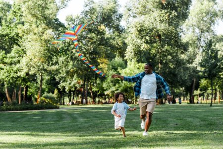 Photo for Happy african american kid running with father and kite in park - Royalty Free Image